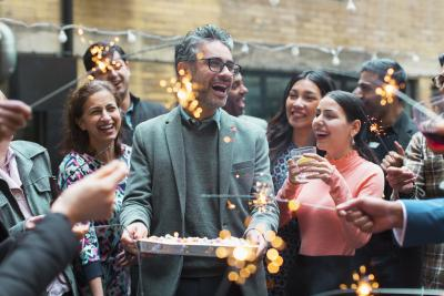 Group of people celebrating with cake and sparklers